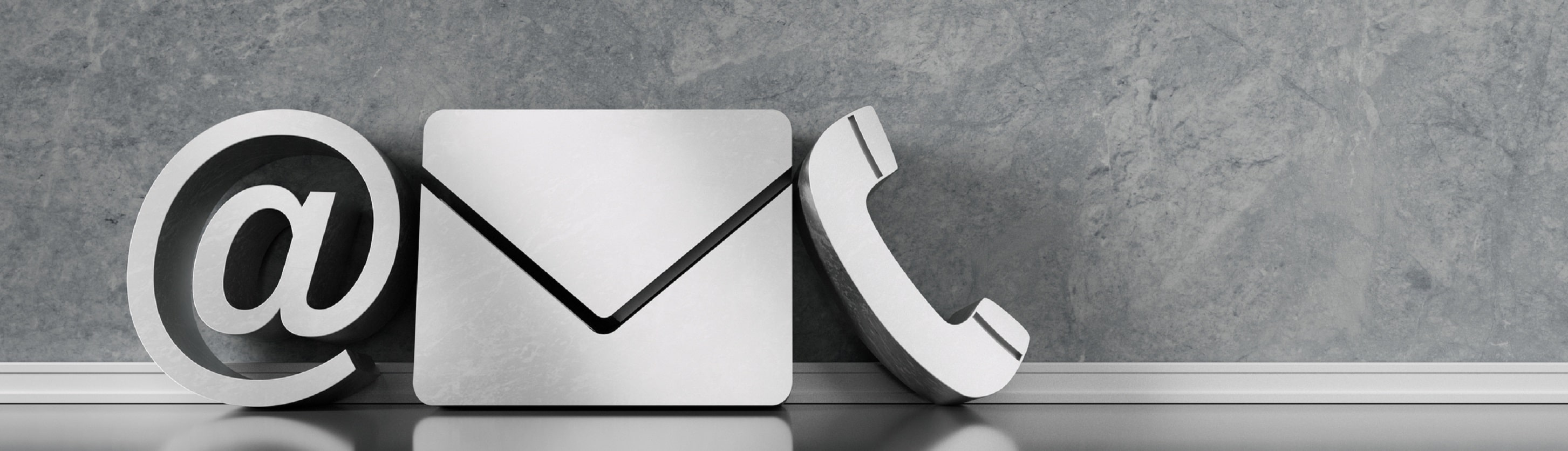 Communication symbols for phone, e-mail and letter standing on the floor against a wall.